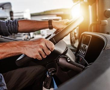 ruky na volante v kabíne kamióna
